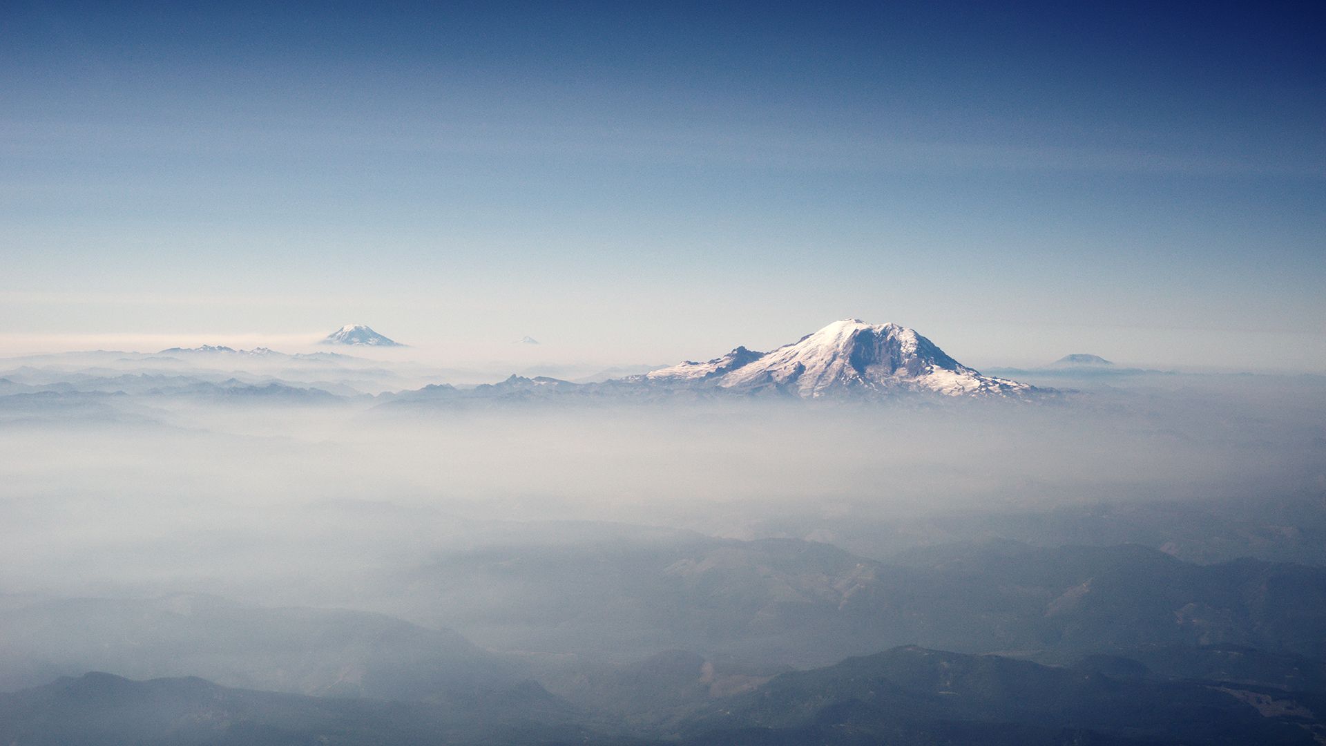Mount_Rainier_and_other_Cascades_mountains_poking_through_clouds.jpg